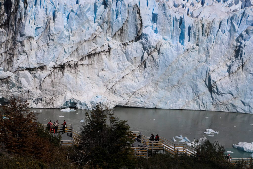 A metal pathway with a few tourists on it sits in front of a glacier in Patagonia
