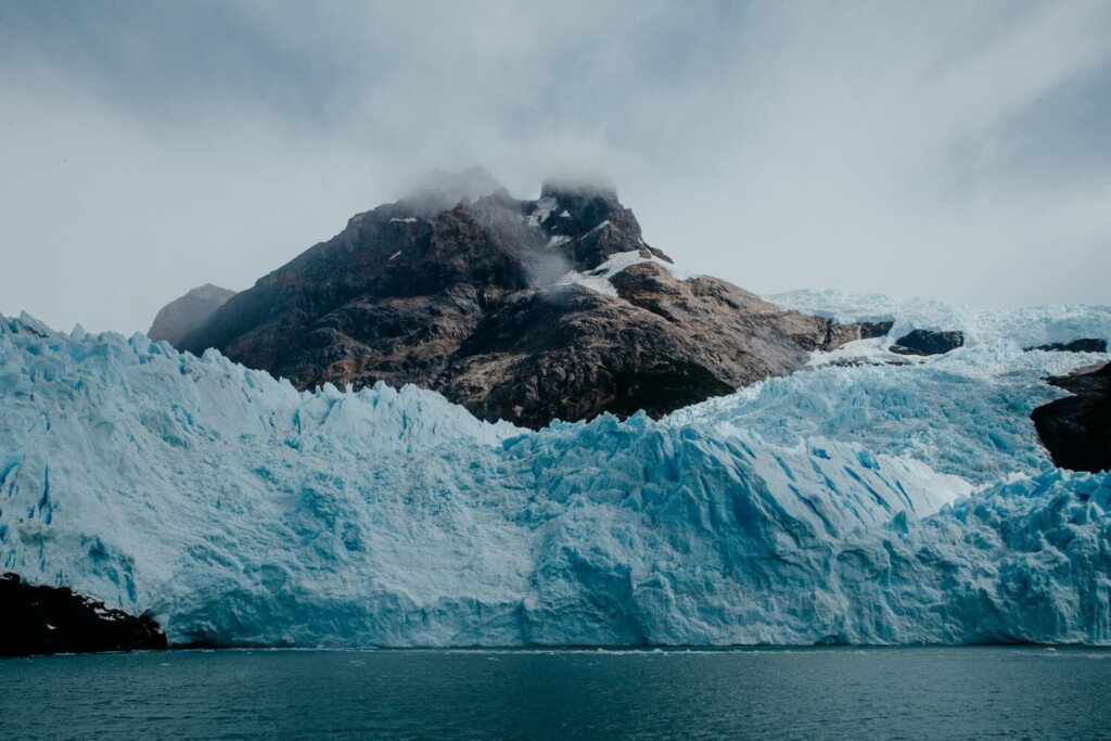 A bright blue glacier sits in front of a gray mountain on a cloudy day