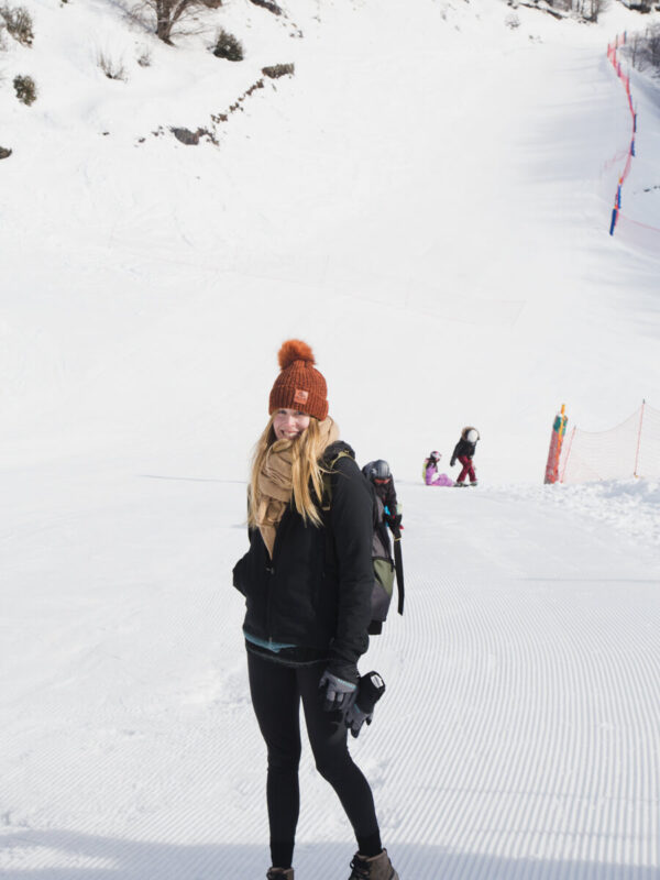 A woman in a black coat and leggings is standing on a ski mountain in the snow
