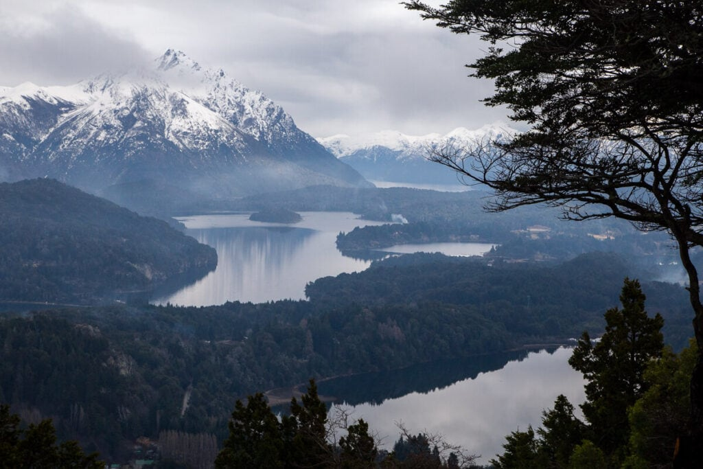 Dark clouds hang over snowy mountains and lakes in Argentina's lake district