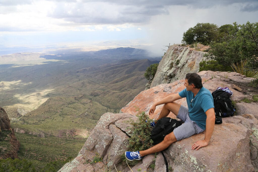 A man sits on a rocky cliff in a blue shirt looking into the distance