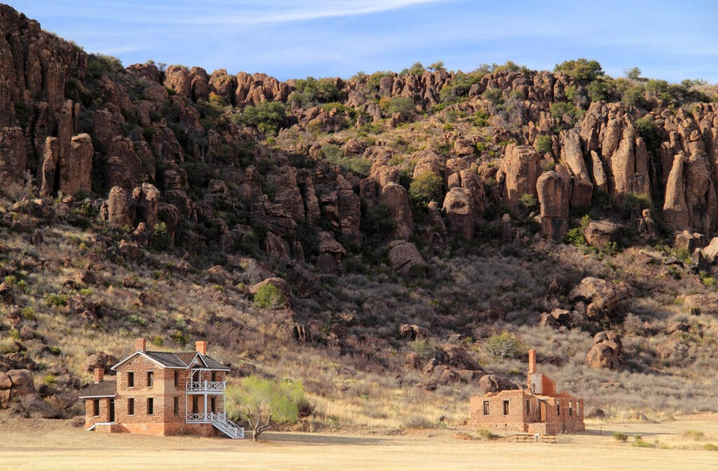 Two brick buildings in a desert with rocky mountains rising up behind them
