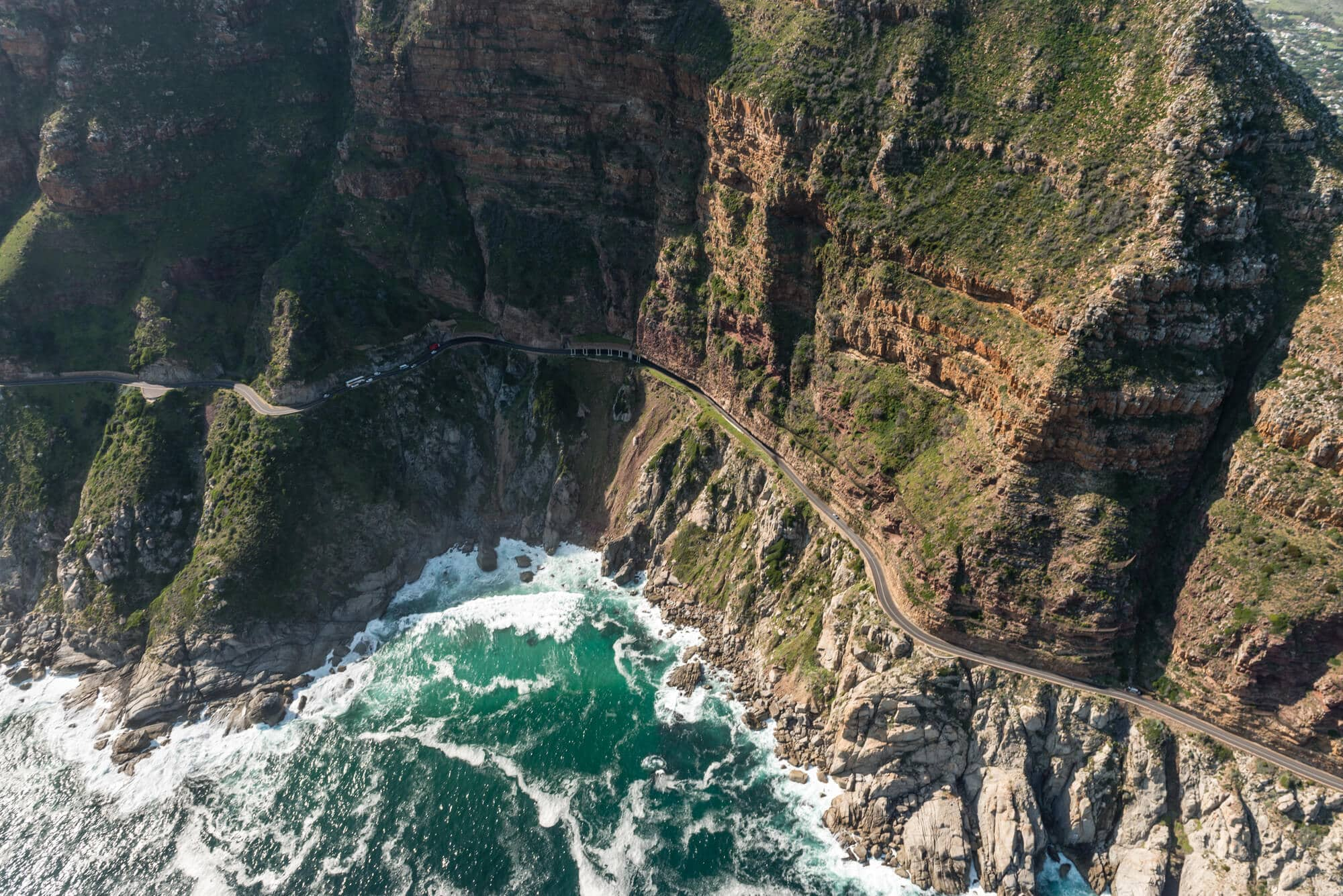 A road snakes along the rocky coast of a green mountain with the ocean below