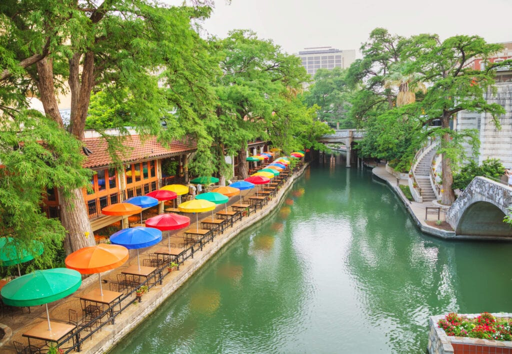 A green river with a sidewalk on both sides and a rainbow of umbrellas over tables of a restaurant on the shore