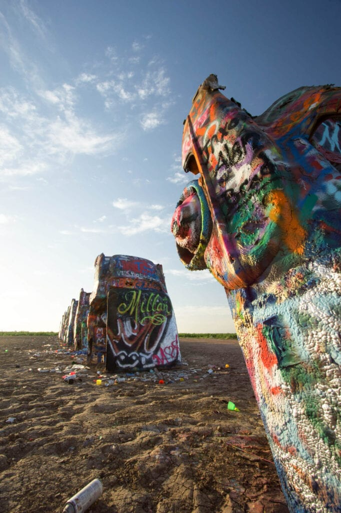 Cadillacs stick out of the desert at a 90 degree angle covered in graffiti