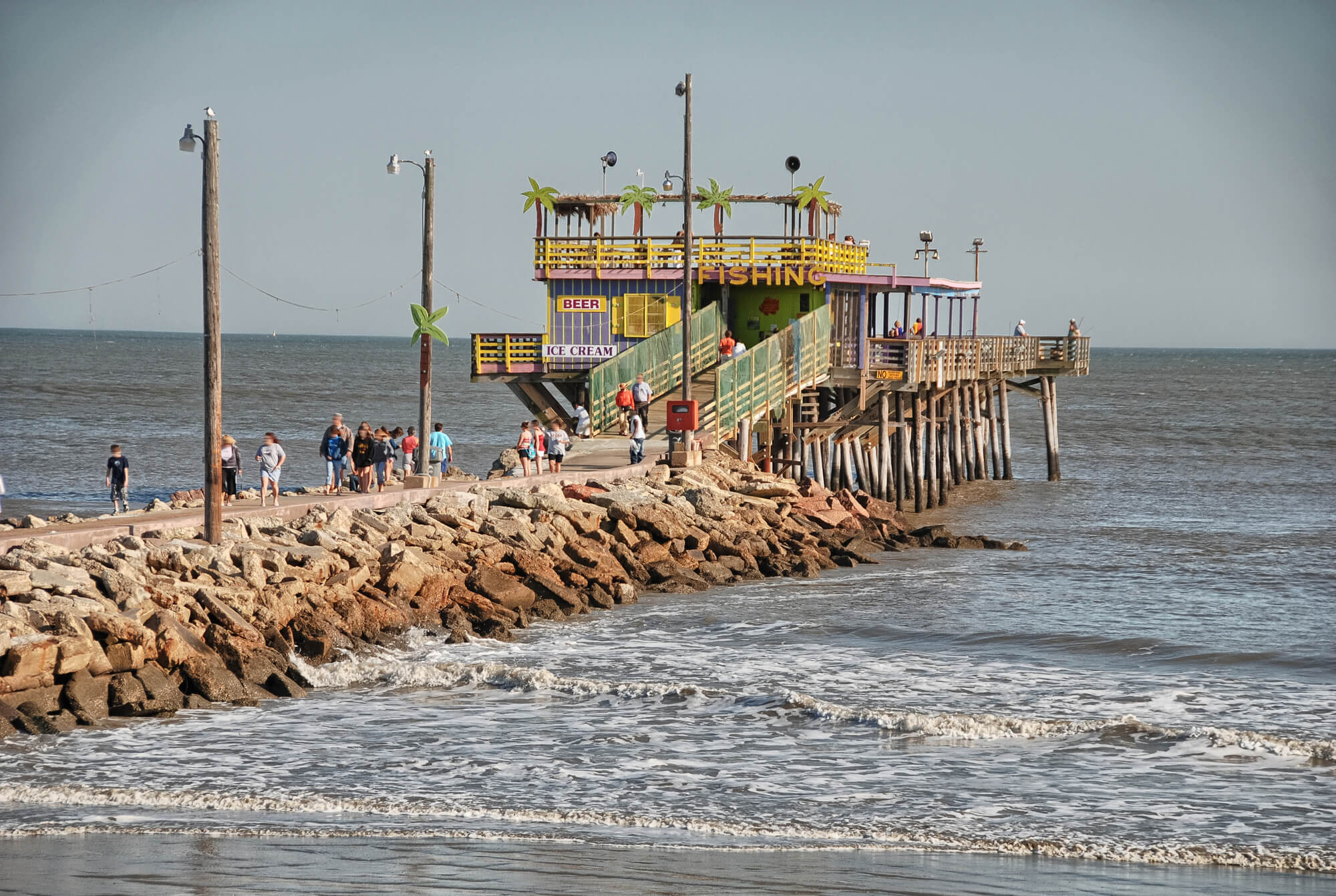 A rocky pier juts out over a brown ocean with a colorful restaurant at the end over the water