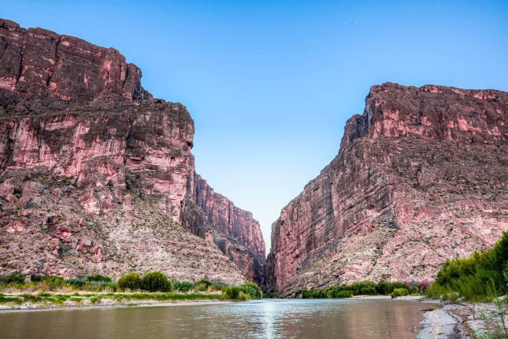 Bright red cliffs frame a canyon with a river flowing through it