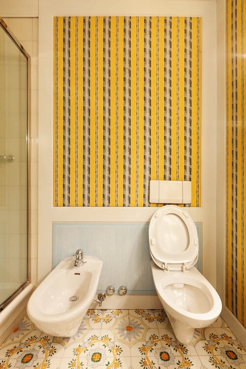 A toilet and a bidet in a bathroom with yellow wallpaper