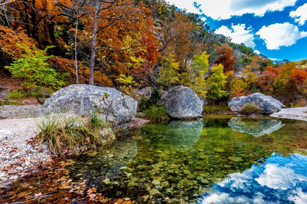 A transparent lake shows the rocks at the bottom with boulders on the shore and orange fall foliage behind them