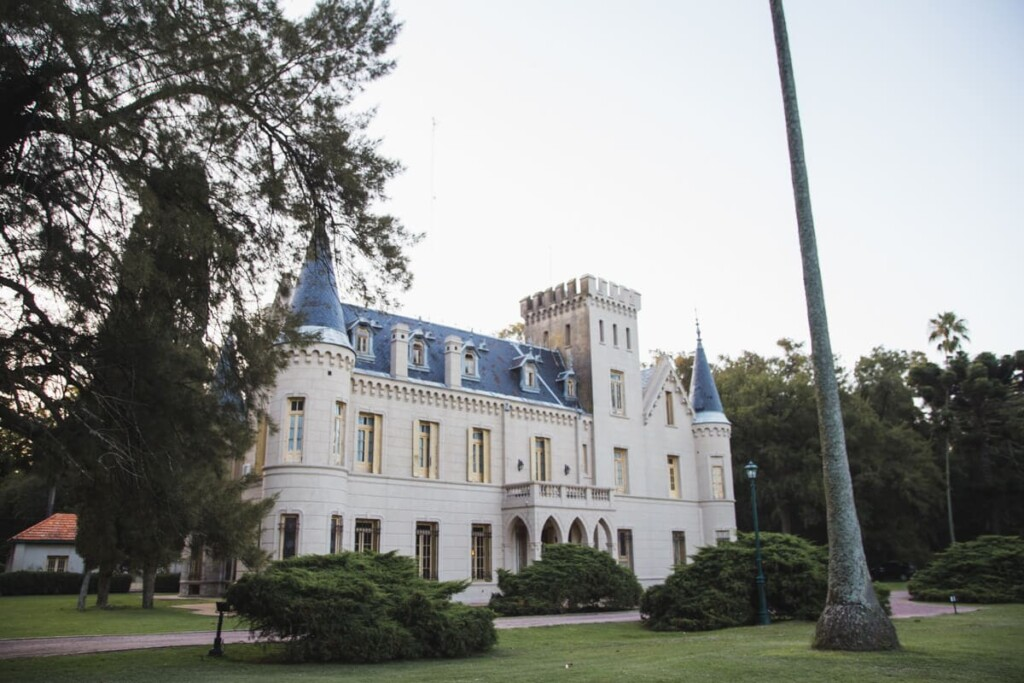 A castle in a green lawn with pine trees