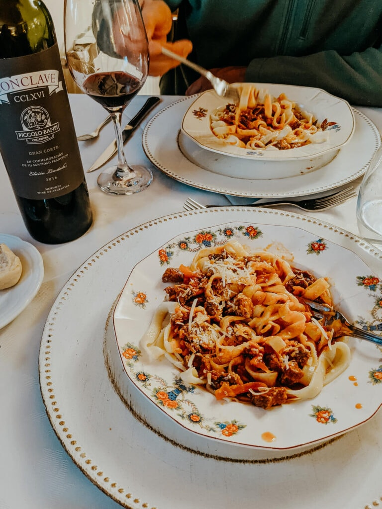 Two bowls of spaghetti in antique bowls and a bottle of wine