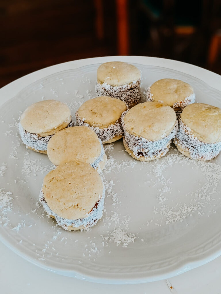 A plate full of alfajor cookies bathed in shaved coconut