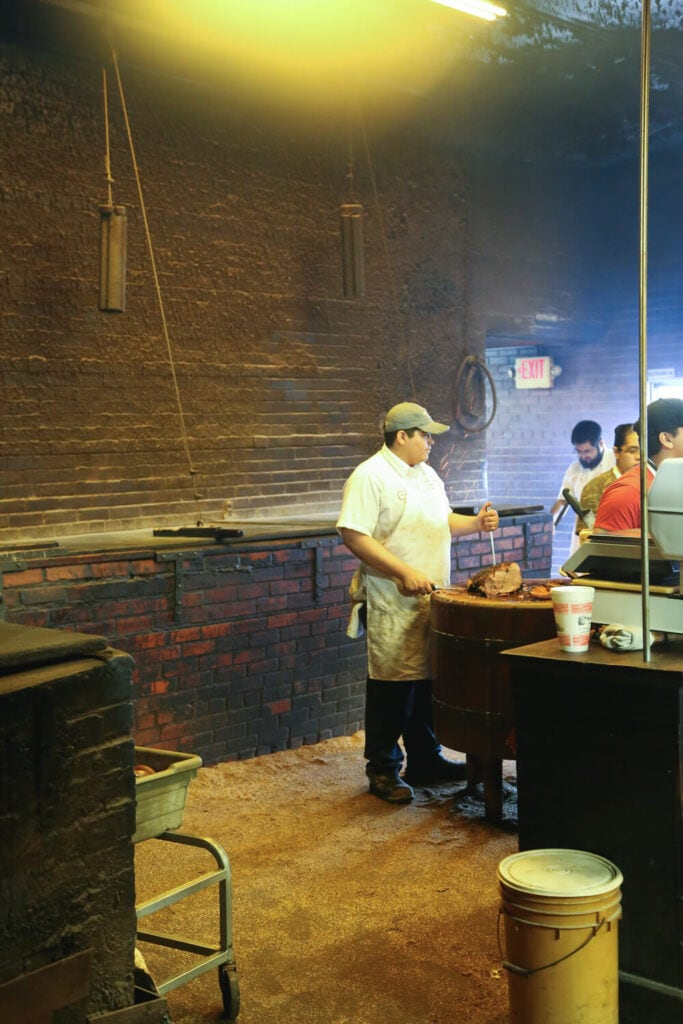 A man in a white apron carves a brisket on a butcher block
