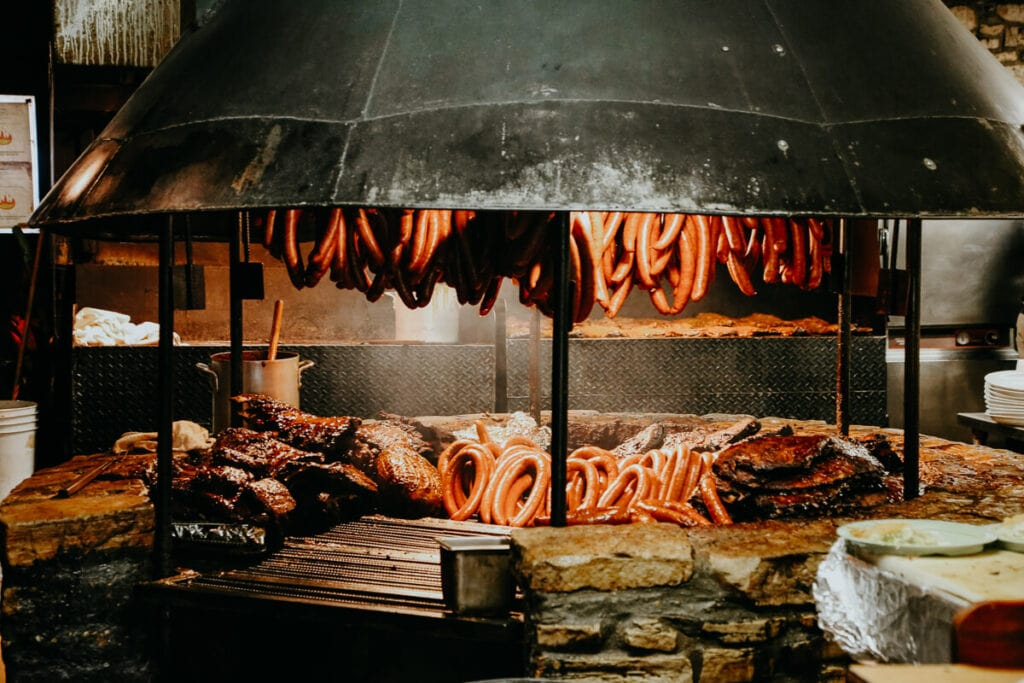 Countless sausage links and briskets on a circular grill