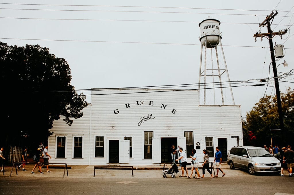 Four people walk in front of a white wooden building with a large metal water tank overhead