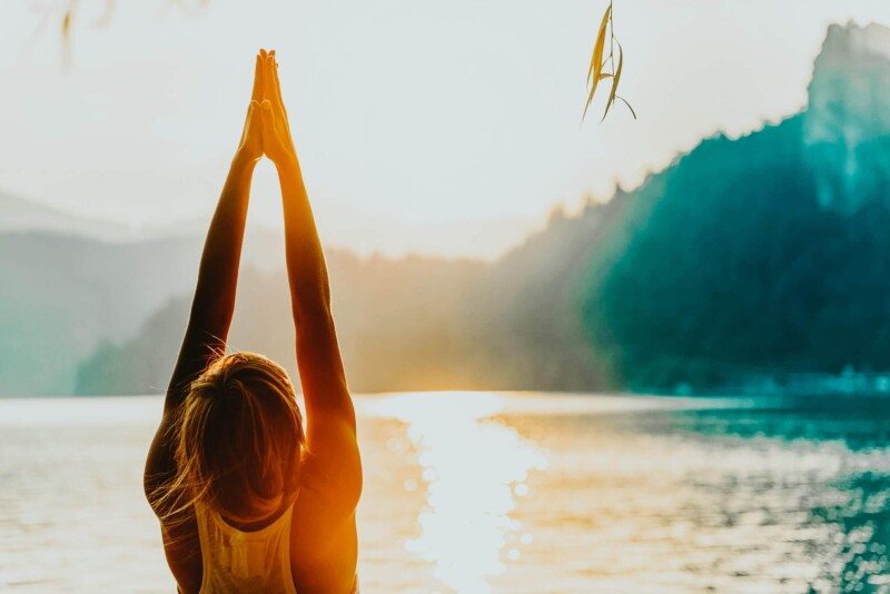 A woman is doing yoga with her hands together overhead with the sun bathing her in orange light in front of a lake