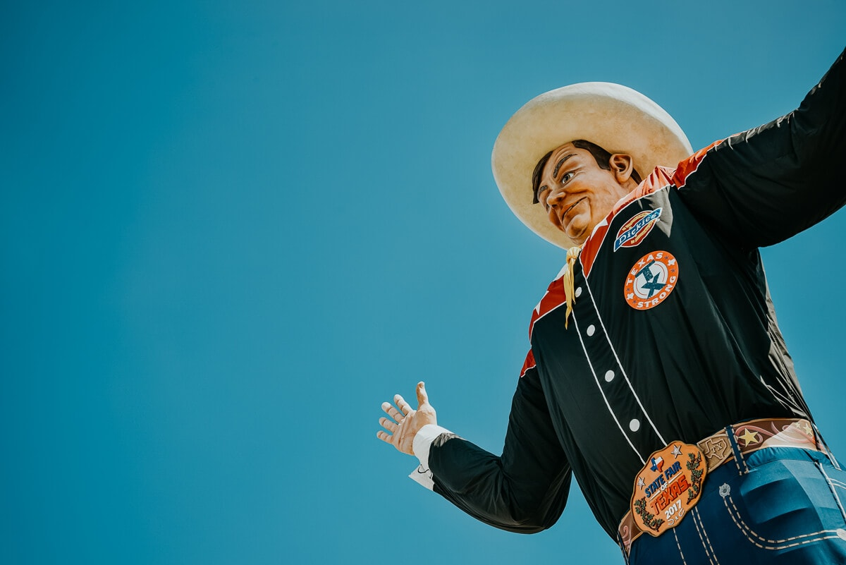 Big Tex, a large statue of a cowboy, stands up in the blue sky