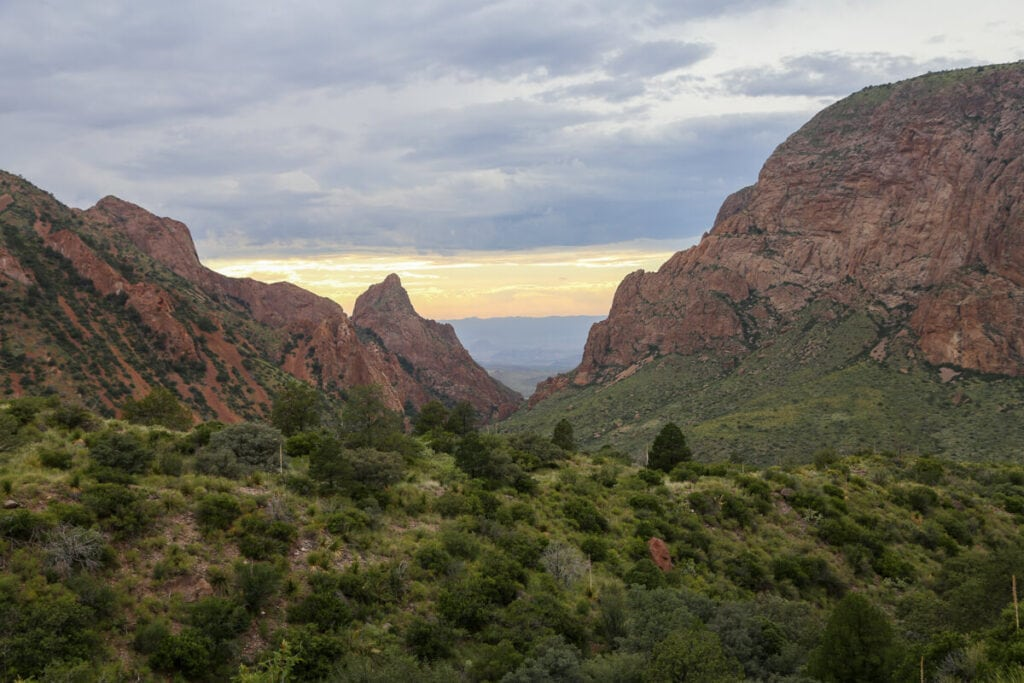 The sunset and a yellow sky tower over red mountains and a green canyon