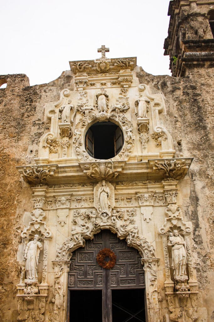 The front facade of a catholic church in a historic mission with a cross on top and statues decorating the facade