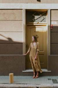 A woman in a yellow dress stands in front of a beige wall and yellow door