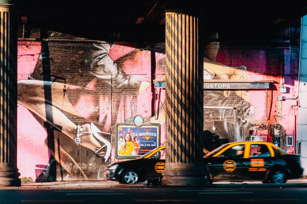 A pink mural of two tango dancers by a road with two taxi cabs driving past