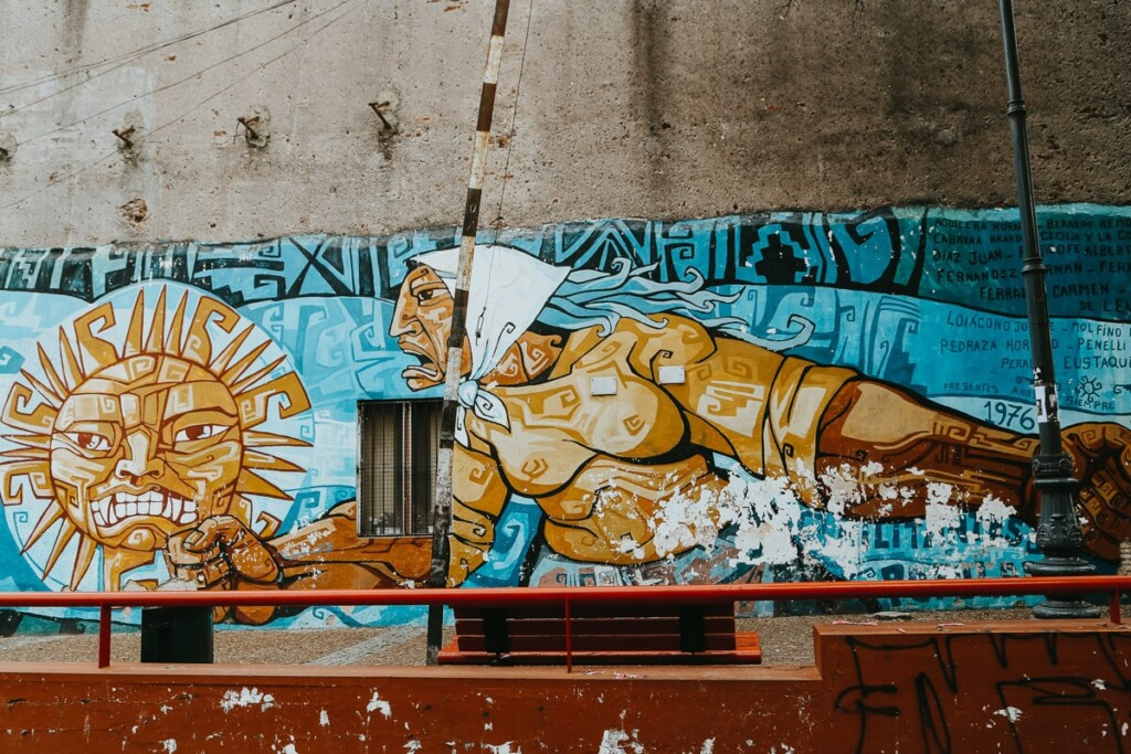 A mural of a woman in a white bandana and yellow shirt with her hand in a fist by a sun