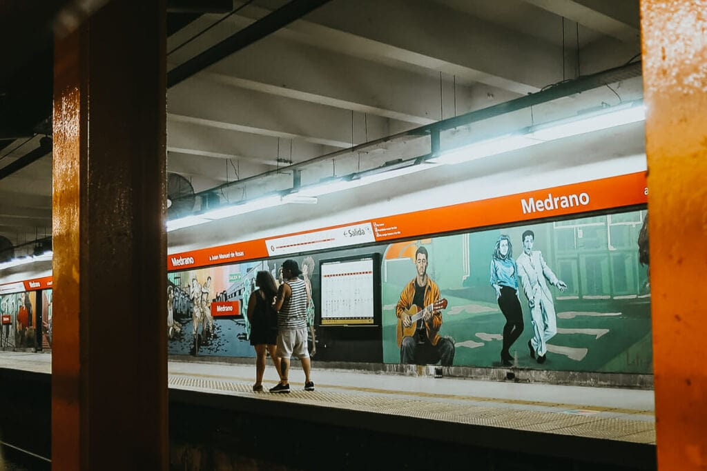A man and a woman walk down a subway platform