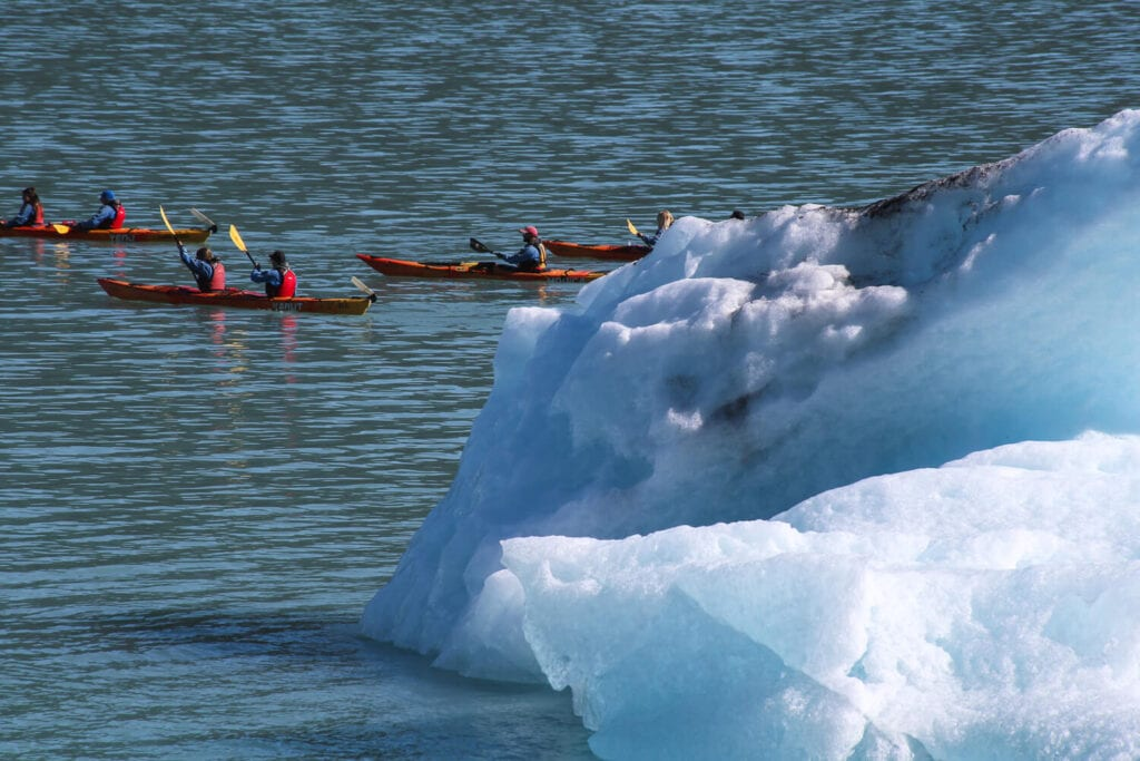 Four red kayaks paddle through the water next to a gigantic iceberg.