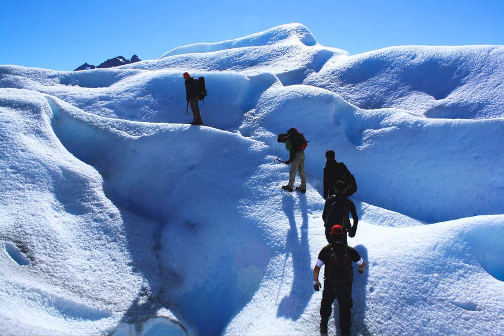5 men with ice picks climb a snow bank on a glacier in El Calafate Argentina