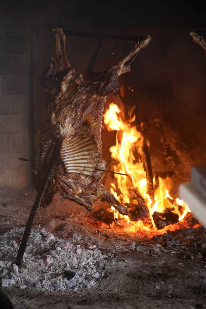 Lamb grilling over a fire hung from a metal cross in Patagonia