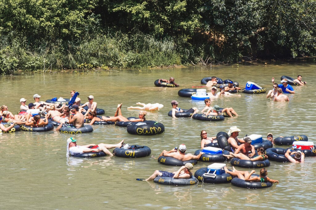 A bunch of people floating on innertubes float down a river