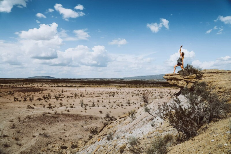 A woman does warrior pose in the desert