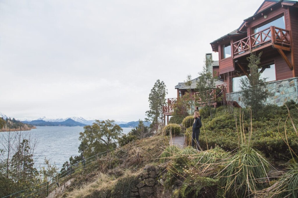 A woman on a sidewalk in front of wood cabins on a lake