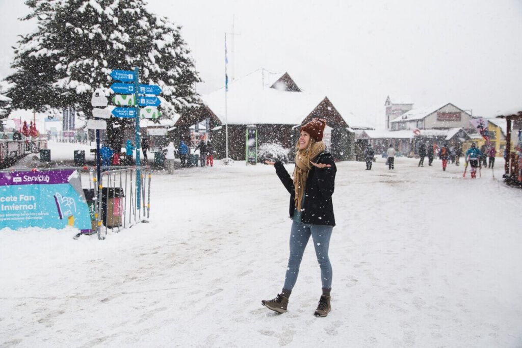 A woman stands in the snow with her hands up catching snowflakes
