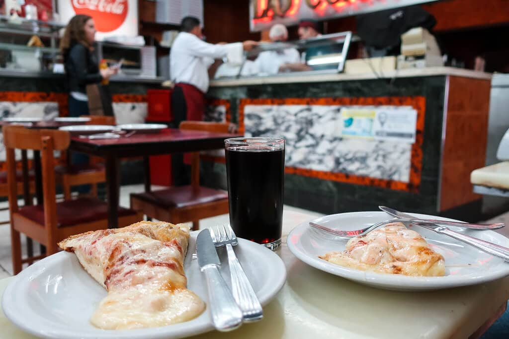 Two plates with cheese pizza on a table