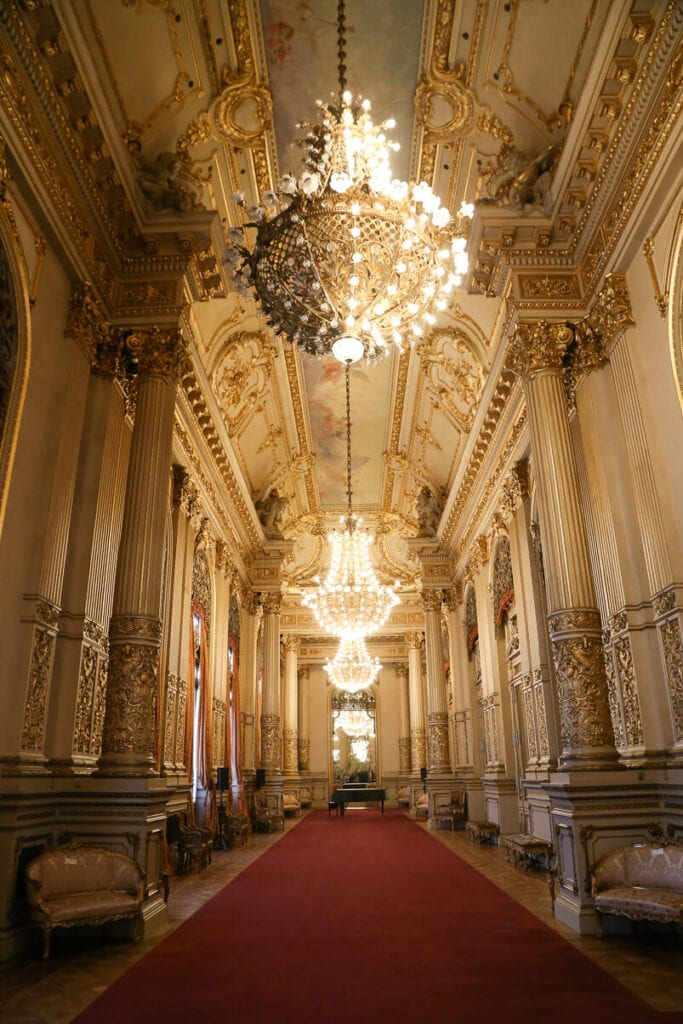 A red carpet in a white and gold hallway with chandeliers
