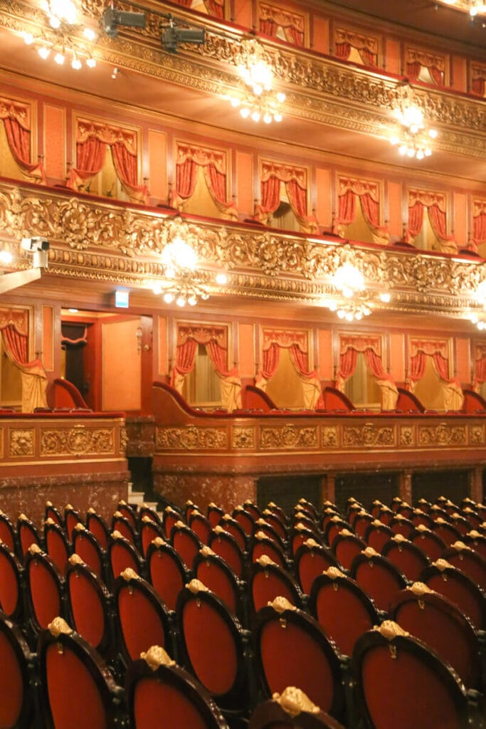 An opera house with red and gold seats and golden detailed balcony seating