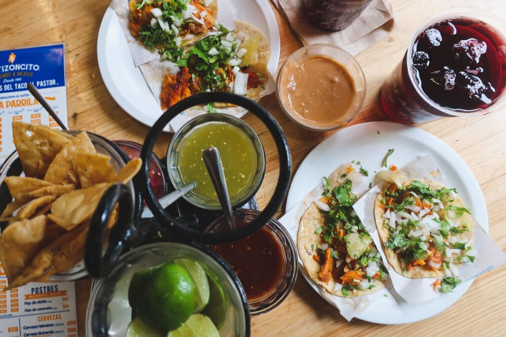 Two plates of tacos surrounded by chips and dips on a wooden table