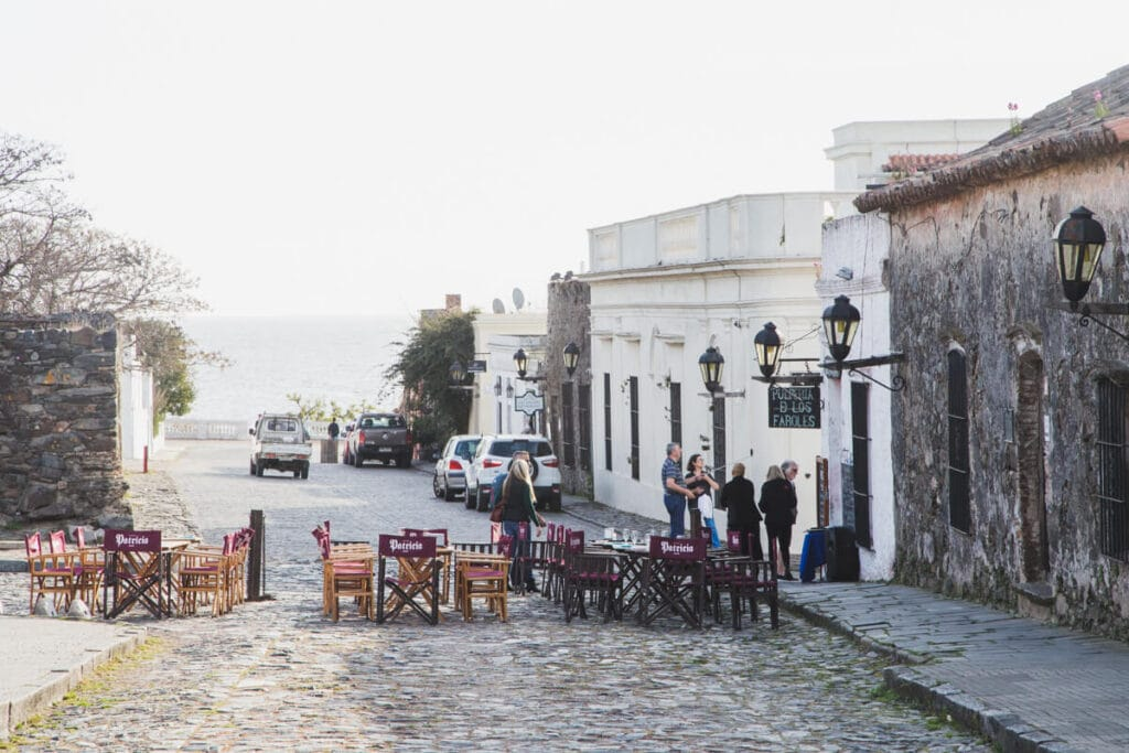 Tables and chairs on a cobblestone street next to colonial buildings