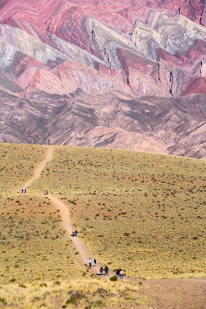 A dirt path winds down a desert landscape towards a red mountain