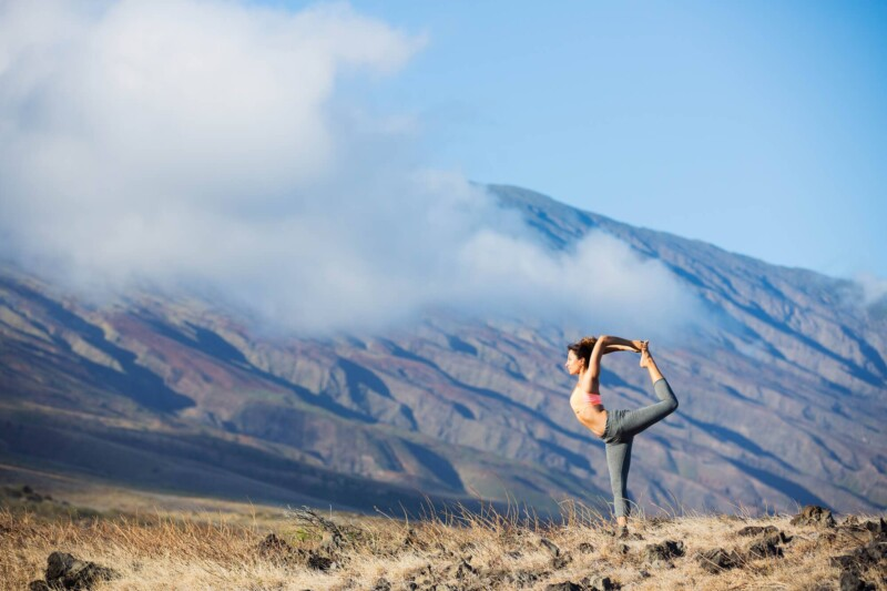 A woman does dancer pose doing yoga in the mountains