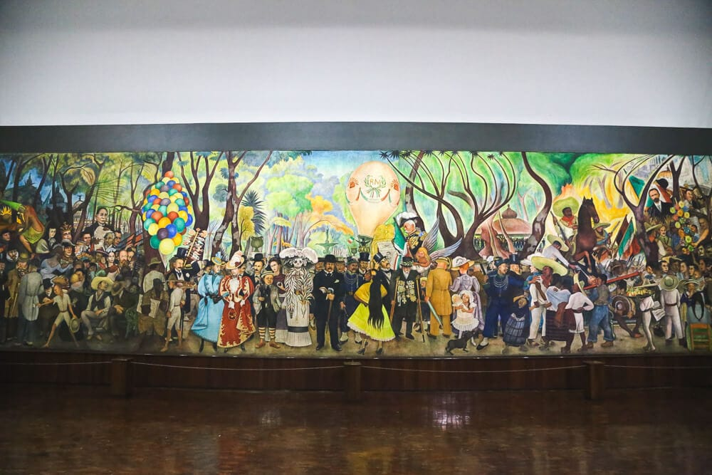 A large mural of Mexican life in a museum