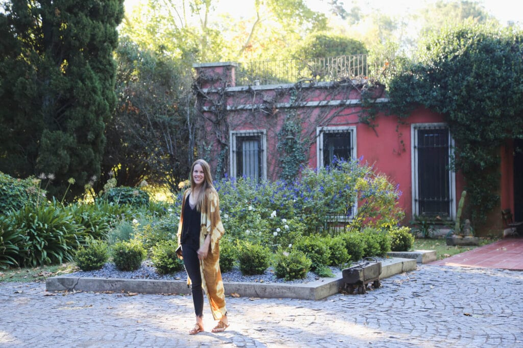 A woman stands on cobblestone in front of a garden and colonial style pink home