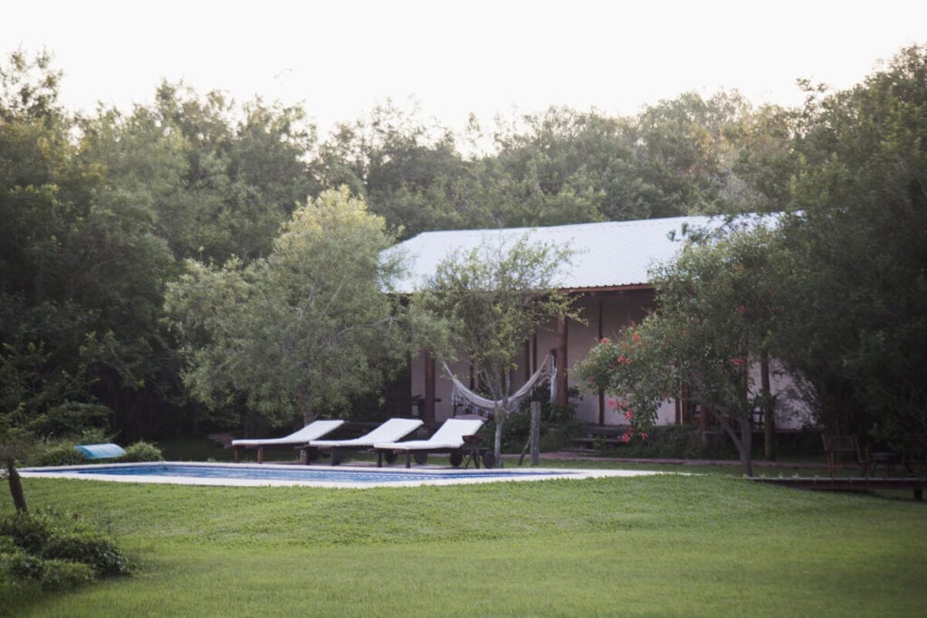 A single story building with a tin roof behind a pool and three lounge chairs