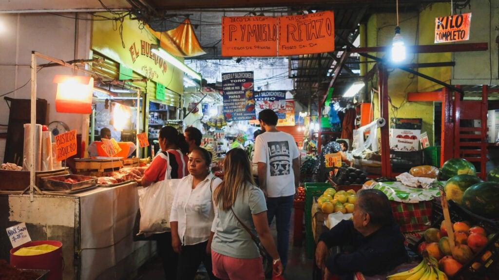 A woman walks through a busy hall down a Mexico City market b fruit and taco vendors