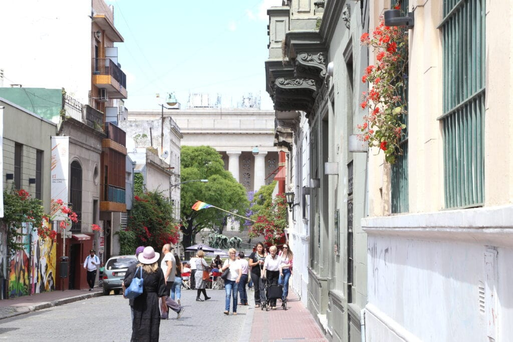 People walking down a street towards a columned building
