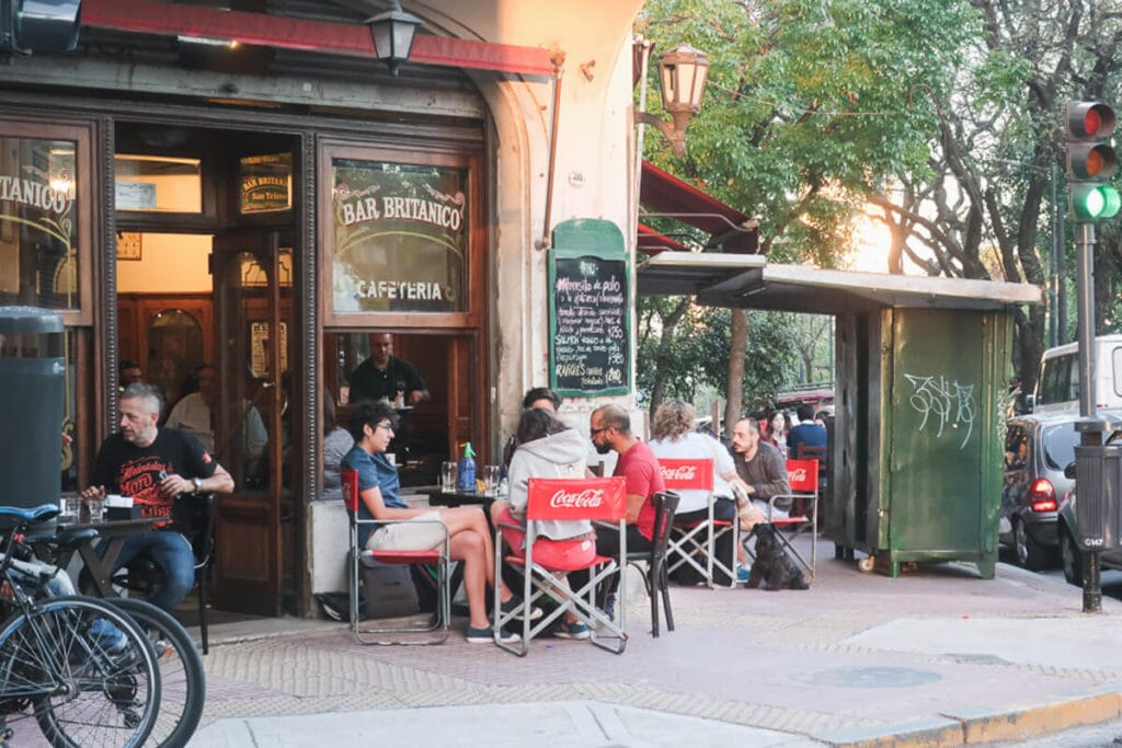 People sit at a sidewalk cafe in front of an old Argentine bar on a street corner