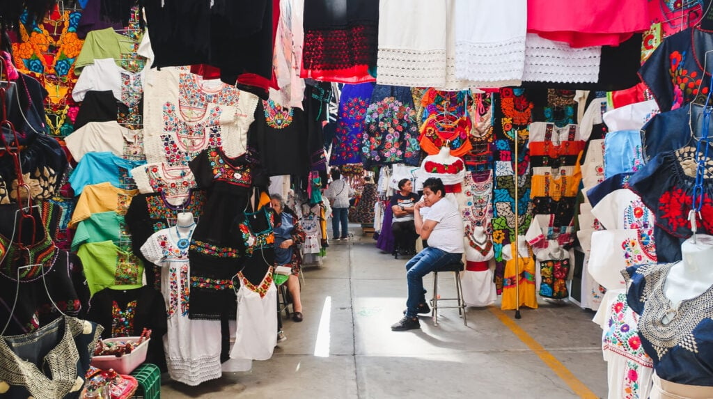 A rainbow of colorfully embroidered blouses hang in a market in Mexico City