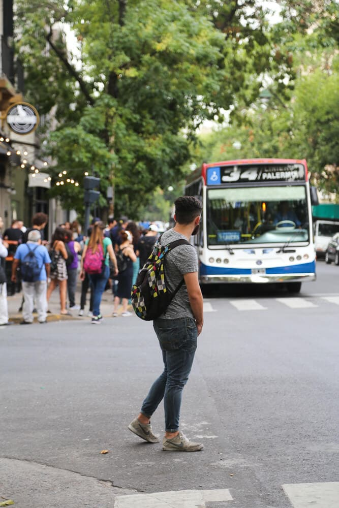 A man waits to cross the street as a city bus drives by