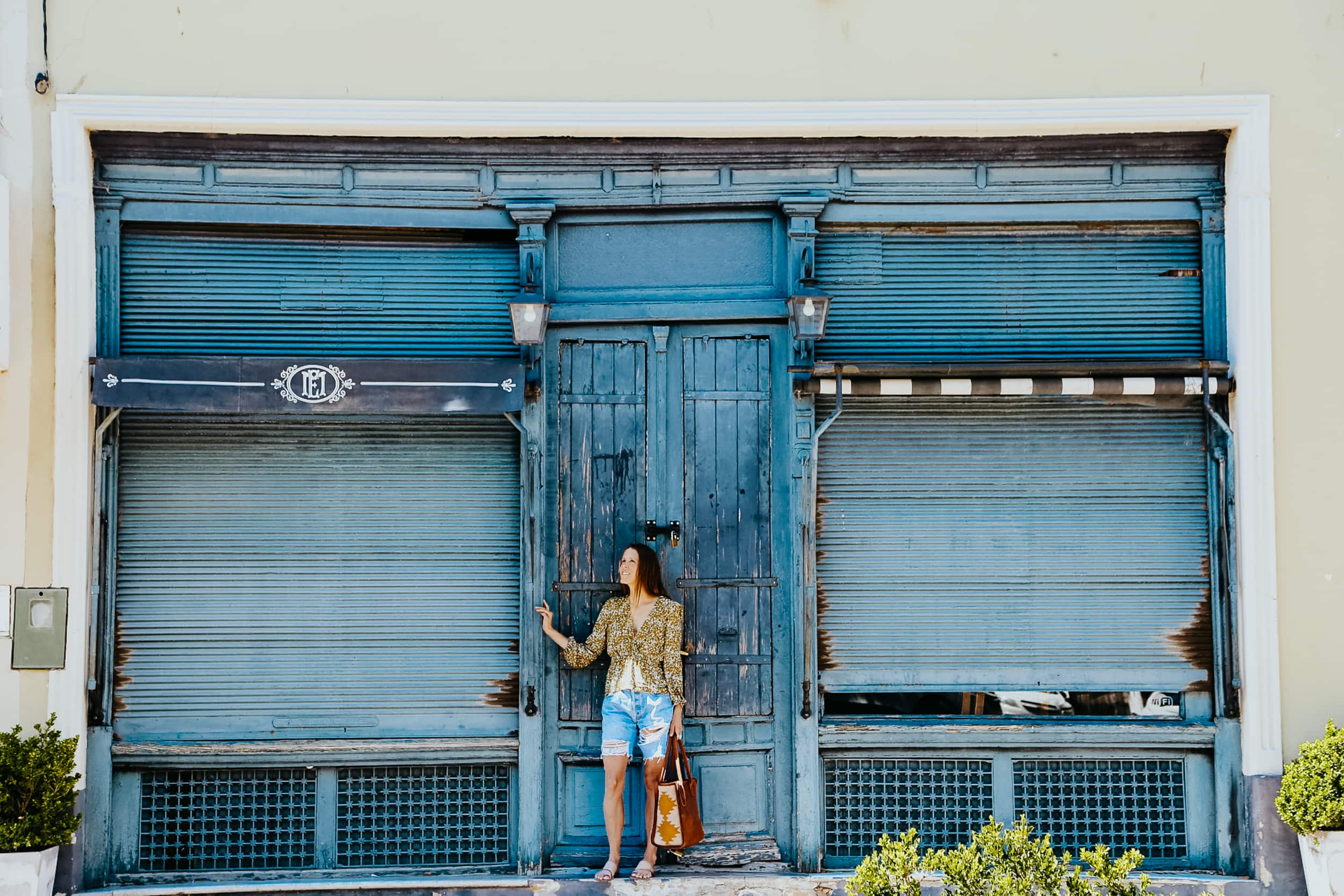 A woman stands in front of a blue door between two windos